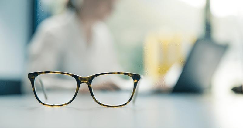 Brille, Hintergrund Frau am Pc arbeiten